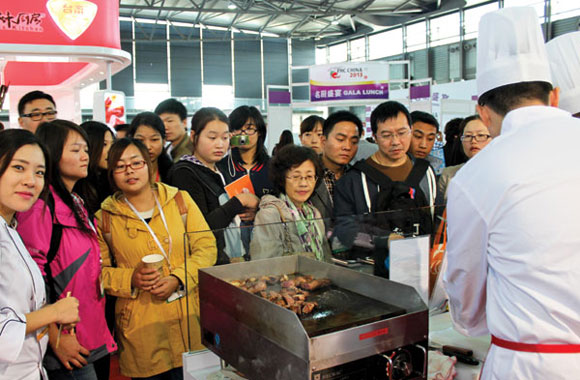 A crowd of buyers gathers around the CBI booth to watch how the chef prepares the grain-finished delicacy.