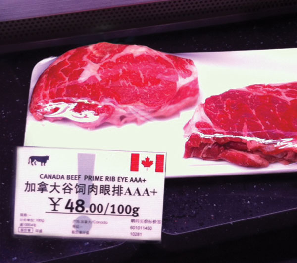 Top-grading Canadian ribeye steaks are prominently displayed at a Shanghai grocery store. The price converts to approximately $38 per pound.