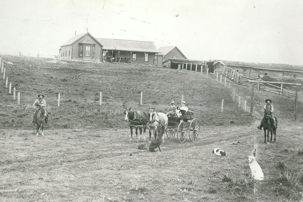 The XC Ranch; from left on horseback: ranch  foreman Ted Cook, John Fraser in the surrey; his wife  Muriel in the back seat; far right on horseback, John Bateman. Photo courtesy Daryl Drew.