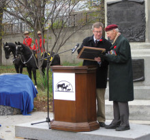 With mounted RCMP in red serge in the background, Ottawa Mayor Jim Watson hands over the Animals in War Proclamation to AIW leader Lloyd Swick, standing in front of the Boer War Monument. Photo by Shalindhi Perera.