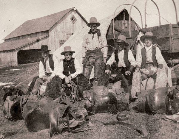 "1906 was the first year Rod trailed cattle from the Rocking P to the John Ware ranch north of Brooks, which he had purchased from Ware's estate. To make sure they had everything they needed, the men did a ""Hudson's Bay Start""—?amassing their saddles, bridles, blankets, bedrolls, tent, harness and repairs for the wagon, axes, shovel, stove and all the cooking things they needed like flour, sugar, salt, beans, bacon, pots and pans and camped out in the yard the night before they left for the two-week trail drive. Apparently this is what the Hudson's Bay men did before they left on a venture so this is where the saying came from. From left: Dave Wheatcroft, Rod Macleay, Joe Case, Doc Mitchell and Chet Mitchell."