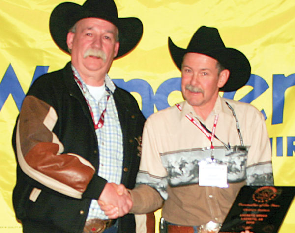 Trophy plaque sponsor Rob Tanner presenting Committee of the Year (Medium Rodeo) winner representative Jake Wiebe on behalf of the La Crete rodeo committee