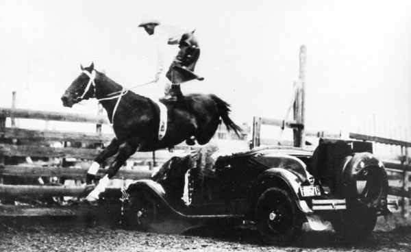 Roman-riding while jumping one of his signature Ford vehicles. Ted Elder jumping a vehicle while standing on one of his Irish Hunter horses; an extremely difficult feat. Photo courtesy Raymond Museum.