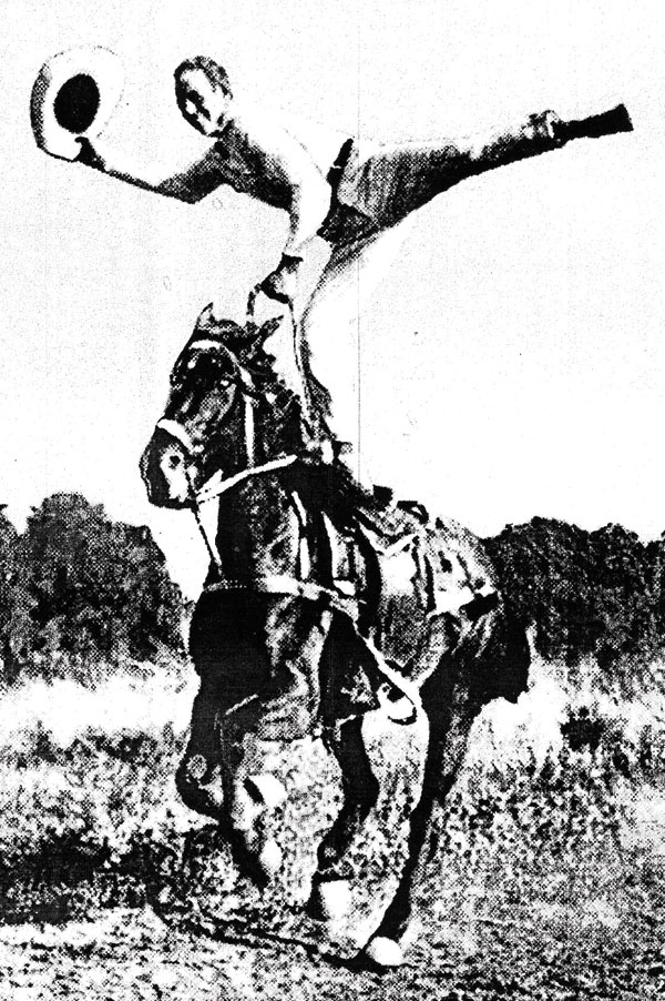 Ted Elder waving his hat while doing a one-leg stand on a galloping horse. Photo courtesy Raymond Museum.