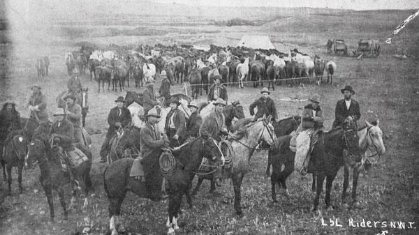 Group of cowboys riding for the LL brand on the annual round up in the NWT, now Alberta and Saskatchewan. Behind them are some of the horses in a rope corral. Although this photo was taken pre-1905 it is reflective of Ray's early experiences.